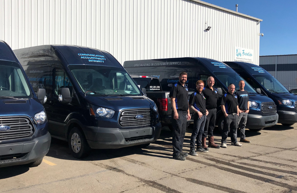 The Aquality plumbing team standing in front of their fleet of vans ready to install or repair plumbing in Calgary